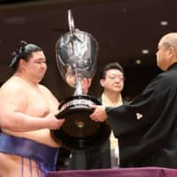 Shodai (left) receives the Emperor's Cup from Japan Sumo Association Chairman Hakkaku after the conclusion of the Autumn Basho. | NIKKAN SPORTS
