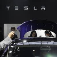 Attendees look at cars at the Tesla booth during the Auto China 2020 show in Beijing on Sunday. | AP