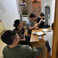Vietnamese students in financial difficulties due to the COVID-19 pandemic have supper at a Tokyo temple that is offering support. | KYODO