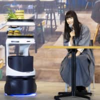 SoftBank Robotics Group Corp.'s Servi food service robot brings food during its unveiling in Tokyo on Monday. | KYODO