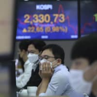 A currency trader watches monitors at the foreign exchange dealing room of the KEB Hana Bank headquarters in Seoul on Tuesday. | AP