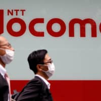 Passersby walk in front of an NTT Docomo store in Tokyo on Tuesday. | REUTERS