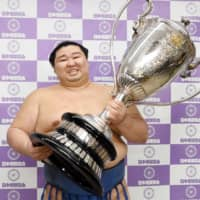 Shodai poses with the Emperor's Cup after winning the Autumn Grand Sumo Tournament on Sunday at Ryogoku Kokugikan. | KYODO