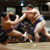 Shodai (right) pushes out Asanoyama during their Day 14 bout on Saturday. | KYODO