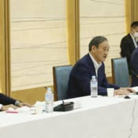 Prime Minister Yoshihide Suga attends a meeting in Tokyo on Friday to discuss the use of the My Number personal identification system and the digitalization of administrative work.   KYODO