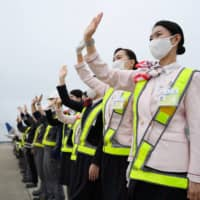 Japan Airlines Co. employees wave to see off a Boeing 767-300ER aircraft at Narita Airport in Chiba Prefecture. | BLOOMBERG
