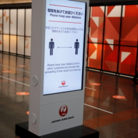 An employee of Japan Airlines wearing a protective face mask walks past near an electric signboard showing information to remind passengers to practice social distancing, at Haneda airport in Tokyo on Oct. 30. | REUTERS