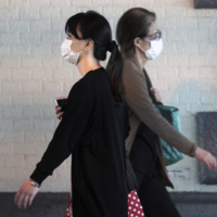 Women wearing protective masks to help curb the spread of the coronavirus walk in Tokyo earlier this month. | AP