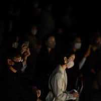 Visitors wearing face masks watch a show from fashion brand Ihnn by designer Chisung Ihn at Tokyo Fashion Week on Oct. 16, 2020. | AFP-JIJI