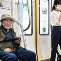 A man listens to the radio while commuting on a train in Tokyo on Oct. 5. | AFP-JIJI
