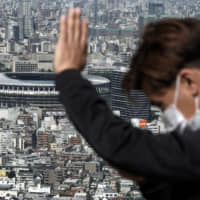A man wearing a protective mask watches a view from an observation deck as the New National Stadium, a venue for the opening and closing ceremonies at the Tokyo 2020 Olympics, is seen in the background on Sept. 30. | AP