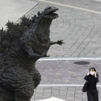 A woman adjusts her face mask as she walks by a statue of Godzilla in Tokyo on Friday. | AP