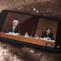 Jun Sawada (left), president and chief executive officer of Nippon Telegraph and Telephone Corp., and Kazuhiro Yoshizawa, president and chief executive officer of NTT Docomo Inc., attend a news conference, as seen on a smartphone in Tokyo on Tuesday. | BLOOMBERG