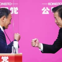 Natsuo Yamaguchi, head of Komeito, greets Prime Minister Yoshihide Suga at Komeito's party convention this week. | KYODO