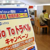 A sign at a travel agency advertises discounts for trips to and from Tokyo in Chiyoda Ward, Tokyo, on Wednesday. | KYODO