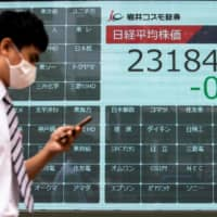 A man walks past a blank electronic board that usually displays Tokyo Stock Exchange share prices after trading was halted due to a glitch on the market in Tokyo on Thursday. | AFP-JIJI