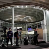 Members of the media are seen working at the empty Tokyo Stock Exchange after the TSE temporarily suspended all trading due to system problems in Tokyo on Thursday. | REUTERS