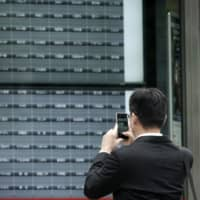 A man takes a photo of a blank electronic stock board at a securities firm in Tokyo on Thursday. Trading on the Tokyo Stock Exchange was suspended because of a problem with the system for relaying market information. | AP
