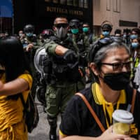 Riot police ask anti-government demonstrators to disperse during a protest in Causeway Bay district in Hong Kong on Thursday.  | BLOOMBERG