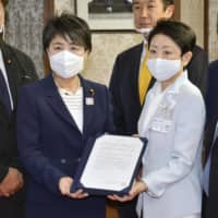 Yayoi Kondo (right), the mayor of Adachi Ward in Tokyo, submits to Justice Minister Yoko Kamikawa on Wednesday a request for measures to be taken against Aum-linked groups. | KYODO