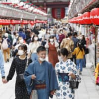 People walk on the Nakamise shopping street in Tokyo's Asakusa district Thursday.   KYODO