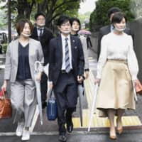 A team of lawyers for a sex business operator in western Japan who is suing the government for being ineligible for the state cash handout program, enter the Tokyo District Court in September. | KYODO