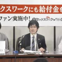 Yusuke Taira (center), the chief of the team of lawyers defending the plaintiff, says the risk of infections shouldn't matter in determining whether or not an industry qualifies for the benefits.  | KYODO