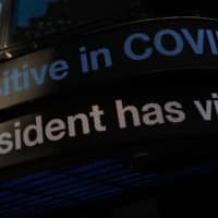 A news ticker displays news of U.S. President Donald Trump testing positive for COVID-19, in New York's Times Square on Friday. | BLOOMBERG