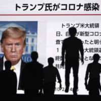 People walk past a screen showing a news report that U.S. President Donald Trump tested positive for COVID-19 on Friday in Tokyo.   AP
