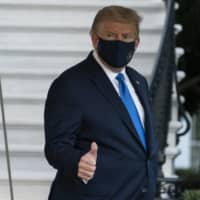 U.S. President Donald Trump gives thumbs up as he leaves the White House to go to Walter Reed National Military Medical Center after he tested positive for COVID-19 on Friday in Washington.   AP