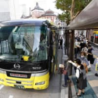 Tourists ride a sightseeing bus in the Marunouchi area near Tokyo Station on Saturday, the first weekend since travel to and from the capital was included in a government subsidy program. | KYODO