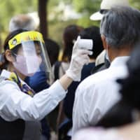 A Hato Bus staff member checks the temperatures of sightseers near Tokyo Station on Saturday. | KYODO