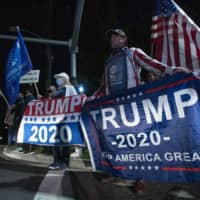 Supporters of U.S. President Donald Trump cheer at the main gate of Walter Reed National Military Medical Center in Bethesda, Maryland, late Friday. | AP