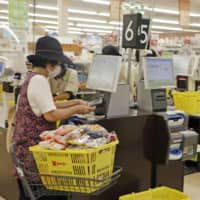 A woman buys groceries at a supermarket in Amami, Kagoshima Prefecture. | KYODO