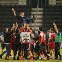 Persepolis players throw their coach in the air to celebrate their win over Saudi Arabia's Al Nassr in the west semifinal of the Asian Champions League on Saturday in Doha. | AFP-JIJI