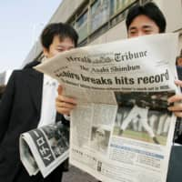People in the Ginza shopping district of Tokyo read an extra edition of the International Herald Tribune following Ichiro Suzuki's record-breaking hit on Oct. 2, 2004. | REUTERS