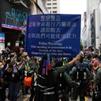 Police ask people to leave during a protest urging the release of 12 Hong Kong activists, detained on the Chinese mainland, who were arrested at sea after attempting to flee to Taiwan, on Chinese National Day in Hong Kong on Thursday.  | REUTERS