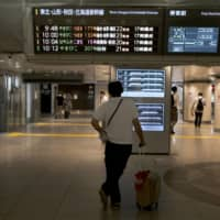 A passenger looks at a departure information board for East Japan Railway Co. bullet trains at Tokyo Station. | BLOOMBERG