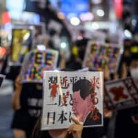 People chant slogans and hold placards during an anti-China protest to mark the 71st anniversary of the founding of the People's Republic of China in Tokyo's Shinjuku district on Saturday. | AFP-JIJI