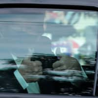 U.S. President Donald Trump gestures from a car as he rides in front of the Walter Reed National Military Medical Center on Sunday.  | REUTERS