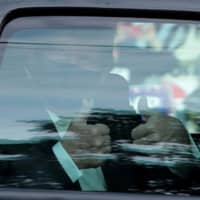 U.S. President Donald Trump gives a thumbs-up from a car as he rides in front of Walter Reed National Military Medical Center, where he is being treated for the coronavirus, in Bethesda, Maryland, on Sunday. | REUTERS