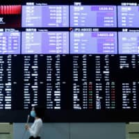 A TV reporter stands in front of a large screen showing stock prices at the Tokyo Stock Exchange after the market opened Friday. | REUTERS