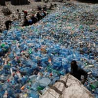 Employees sort plastic bottles at the Weeco plastic recycling factory in the Athi River industrial zone near Nairobi, Kenya in 2019.  | REUTERS