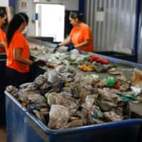 Workers separate different types of plastic at an Extruplas plant in Seixal, Portugal. | REUTERS