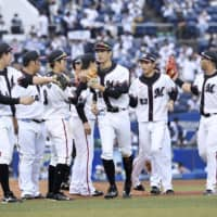 Marines players celebrate a win against Seibu on Sunday in Chiba. Lotte's Tuesday game against the Buffaloes is scheduled to go on despite several people in the organization testing positive for the coronavirus. | KYODO