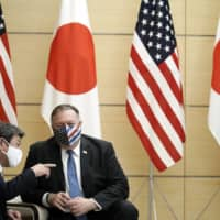 U.S. Secretary of State Mike Pompeo and Foreign Minister Toshimitsu Motegi talk prior to a meeting with Prime Minister Yoshihide Suga, at the Prime Minister's Office on Tuesday. | POOL / VIA AP