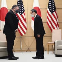 Prime Minister Yoshihide Suga and U.S. Secretary of State Mike Pompeo greet each other prior to their meeting at the Prime Minister's Office on Tuesday.  | PHOTO / VIA AP