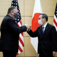 Prime Minister Yoshihide Suga and U.S. Secretary of State Mike Pompeo greet each other prior to their meeting at the Prime Minister's Office on Tuesday.  | POOL / VIA REUTERS