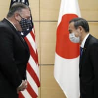 U.S. Secretary of State Mike Pompeo greets Prime Minister Yoshihide Suga prior to a meeting at the Prime Minister's Office in Tokyo on Tuesday. | AP / VIA BLOOMBERG