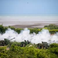 Howitzers fire munitions during a military exercise in Taichung, Taiwan, in July. The drills are aimed at repelling a Chinese invasion across the Taiwan Strait. | BLOOMBERG